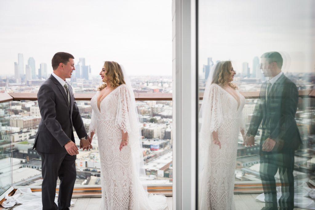 Bride and groom reflected in glass door of William Vale Hotel terrace