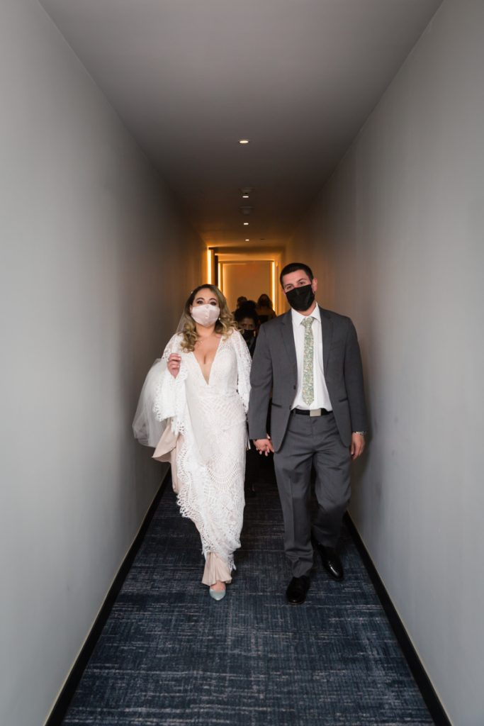 Bride and groom wearing masks and walking down William Vale Hotel hallway