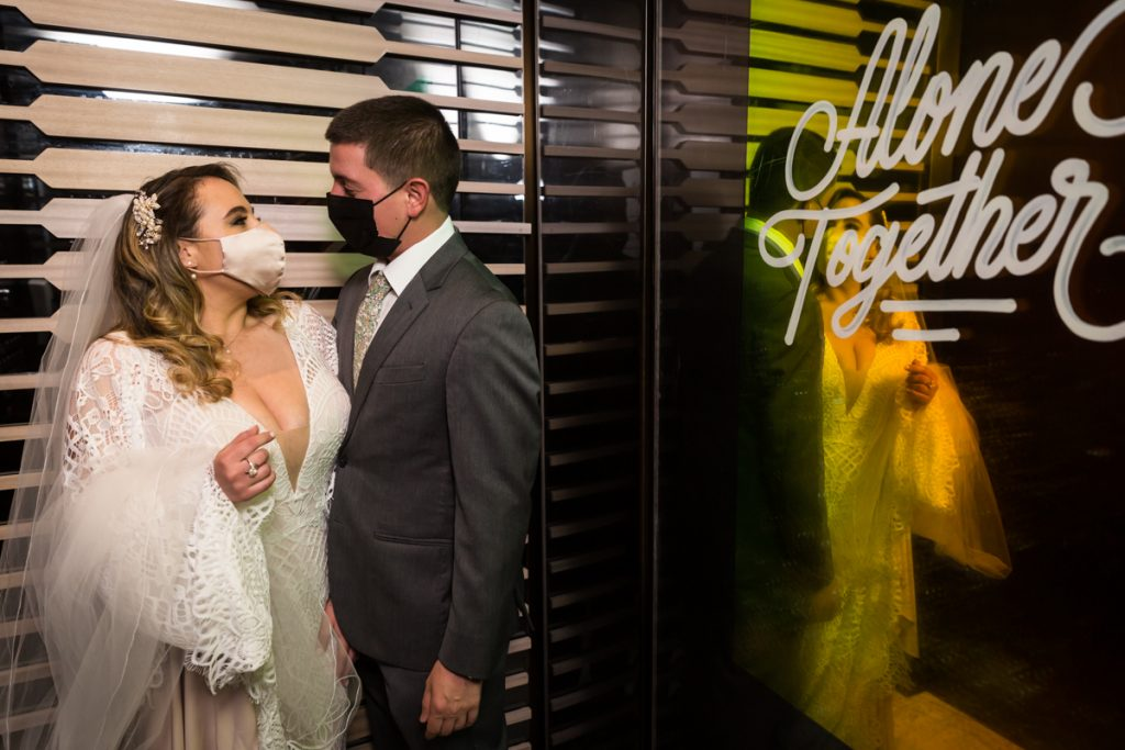 Bride and groom wearing masks in William Vale Hotel elevator