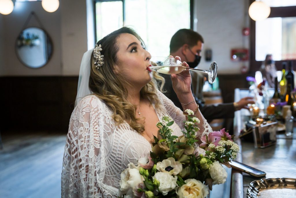 Bride drinking glass of champagne at Brooklyn Winery