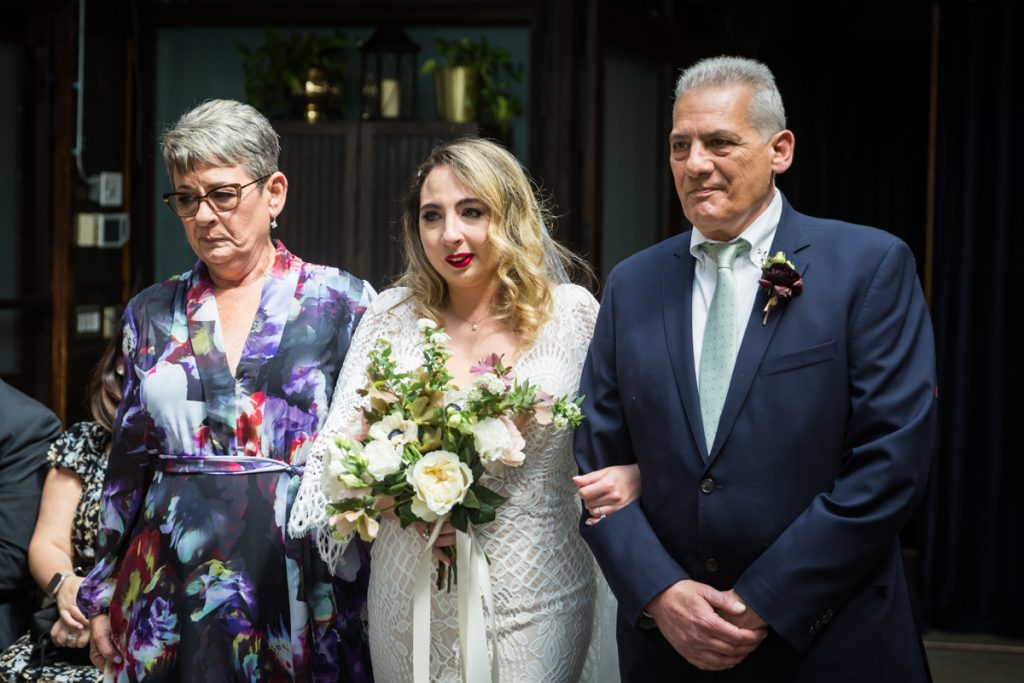 Bride escorted by parents down aisle at Brooklyn Winery