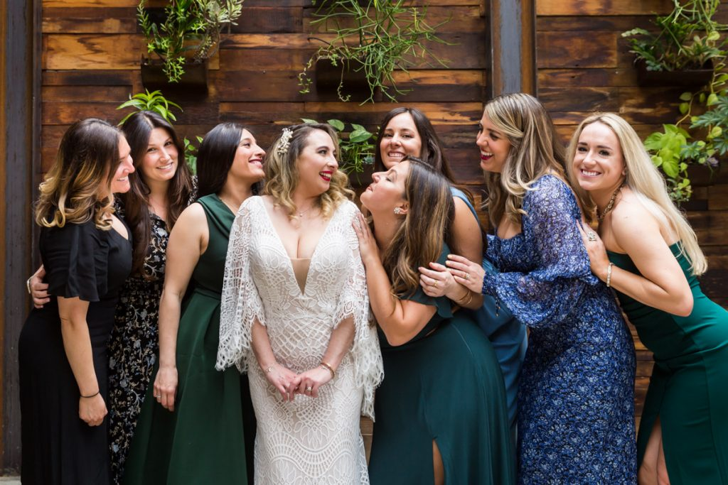Bride and female guests in front of wood wall with plants