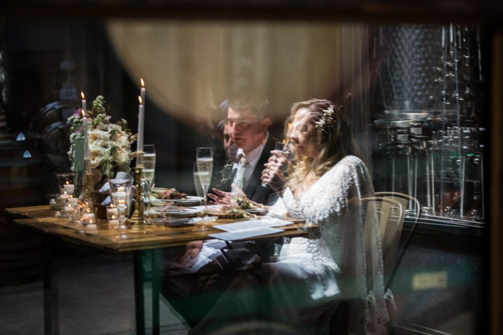 Reflection of bride and groom in glass during Brooklyn Winery wedding reception