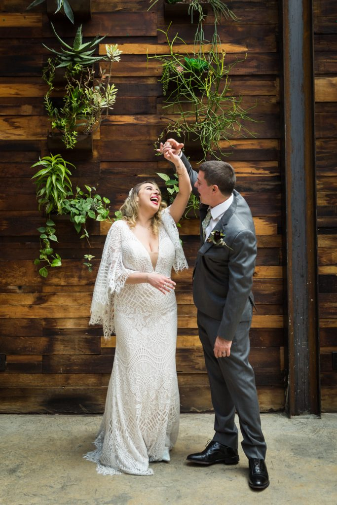 Brooklyn Winery wedding photos of bride and groom dancing in front of wall of plants