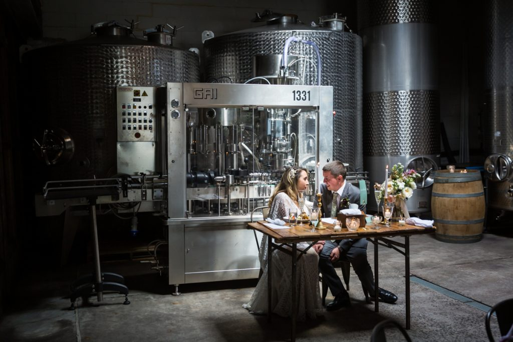 Brooklyn Winery wedding photos of bride and groom seated in front of industrial equipment