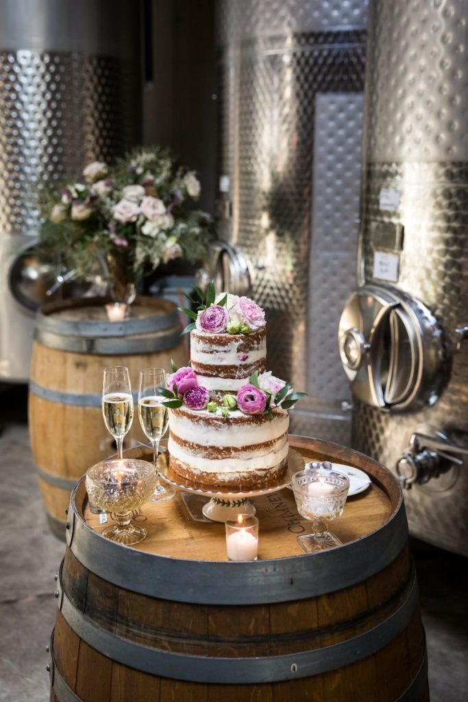 Wedding cake and champagne glasses on a barrel
