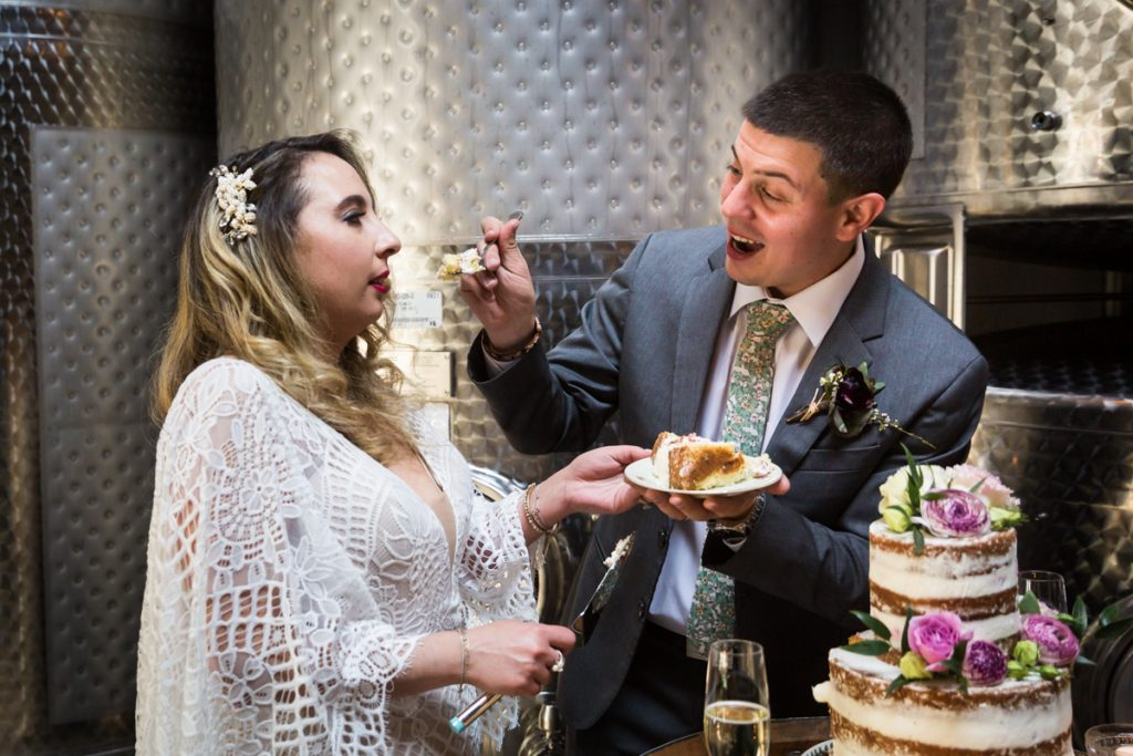 Groom feeding cake to bride during Brooklyn Winery wedding reception