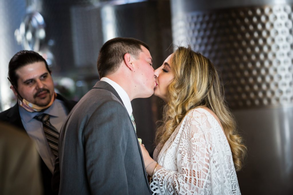 Bride and groom kissing in front of guest during Brooklyn Winery wedding