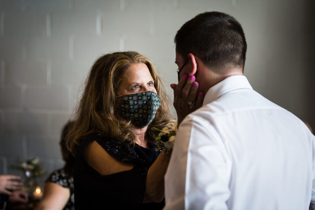 Mother touching groom's cheek and wearing mask