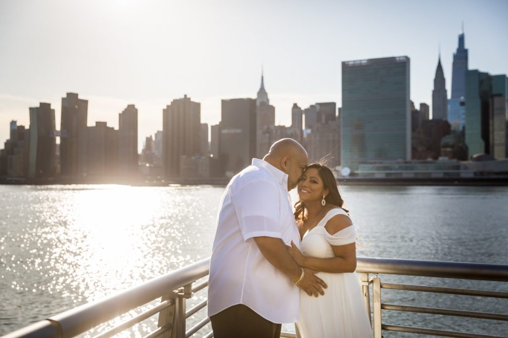 Husband kissing pregnant wife along waterfront during a Long Island City maternity portrait session