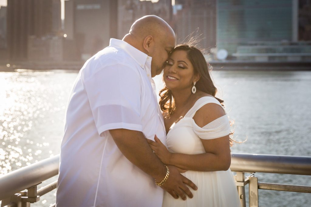 Couple hugging in front of NYC waterfront during a Long Island City maternity portrait session
