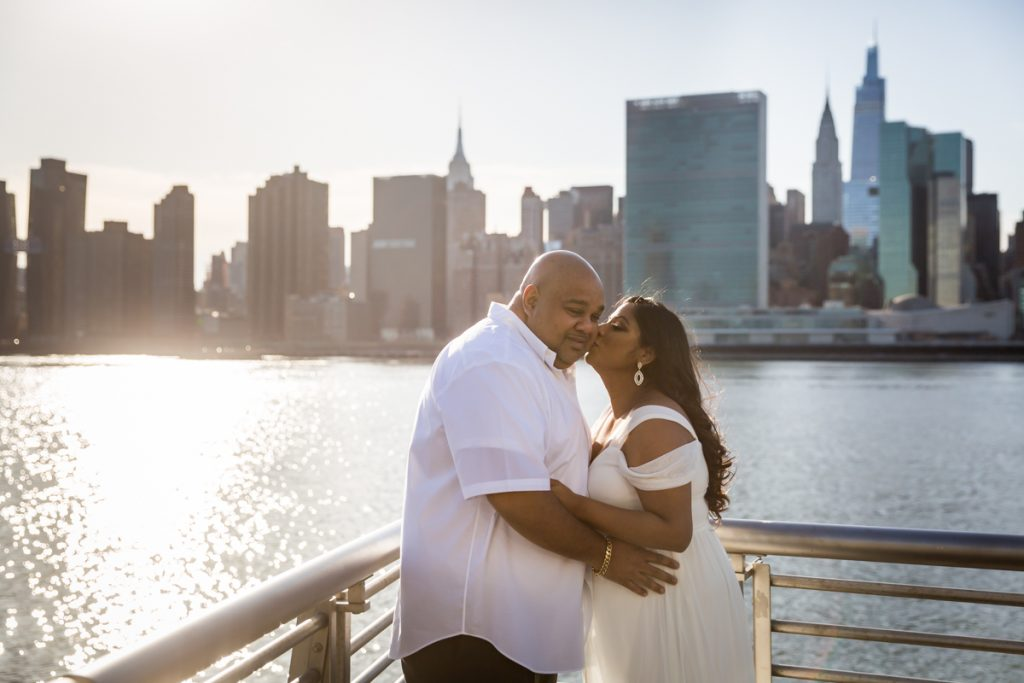 Pregnant woman kissing man's cheek during a Long Island City maternity portrait session
