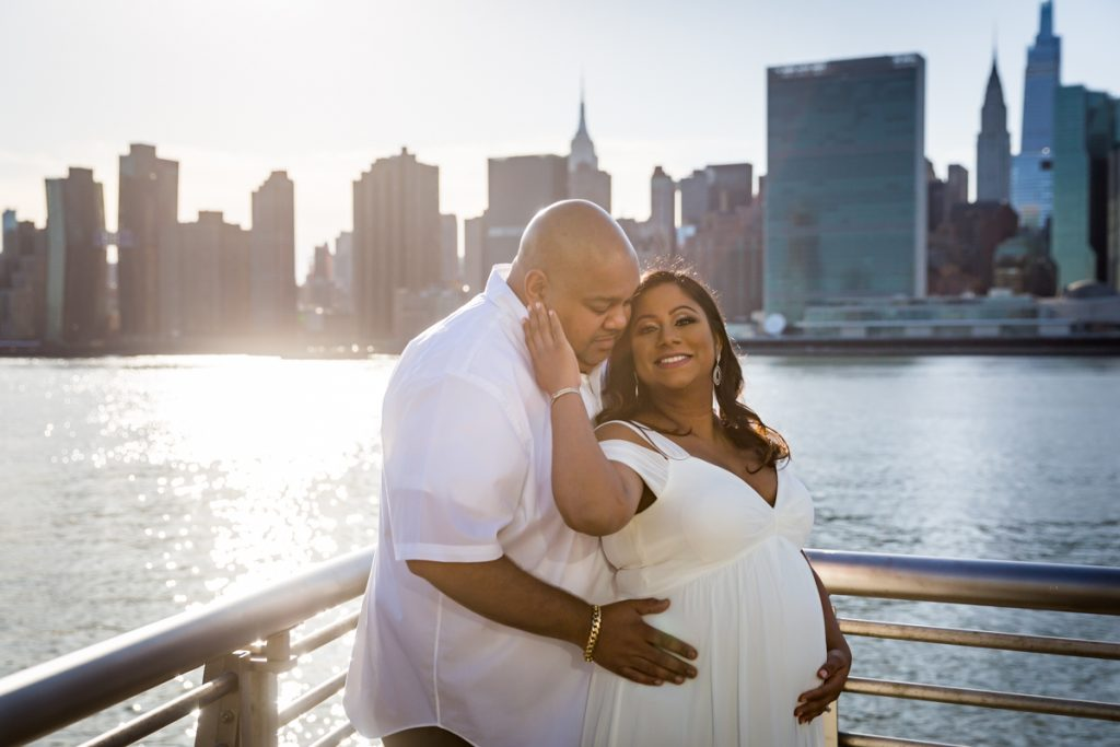Couple posing along NYC waterfront during a Long Island City maternity portrait session