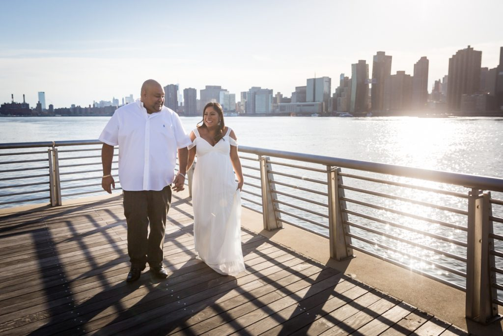 Couple walking along boardwalk at Gantry Plaza State Park during a Long Island City maternity portrait session