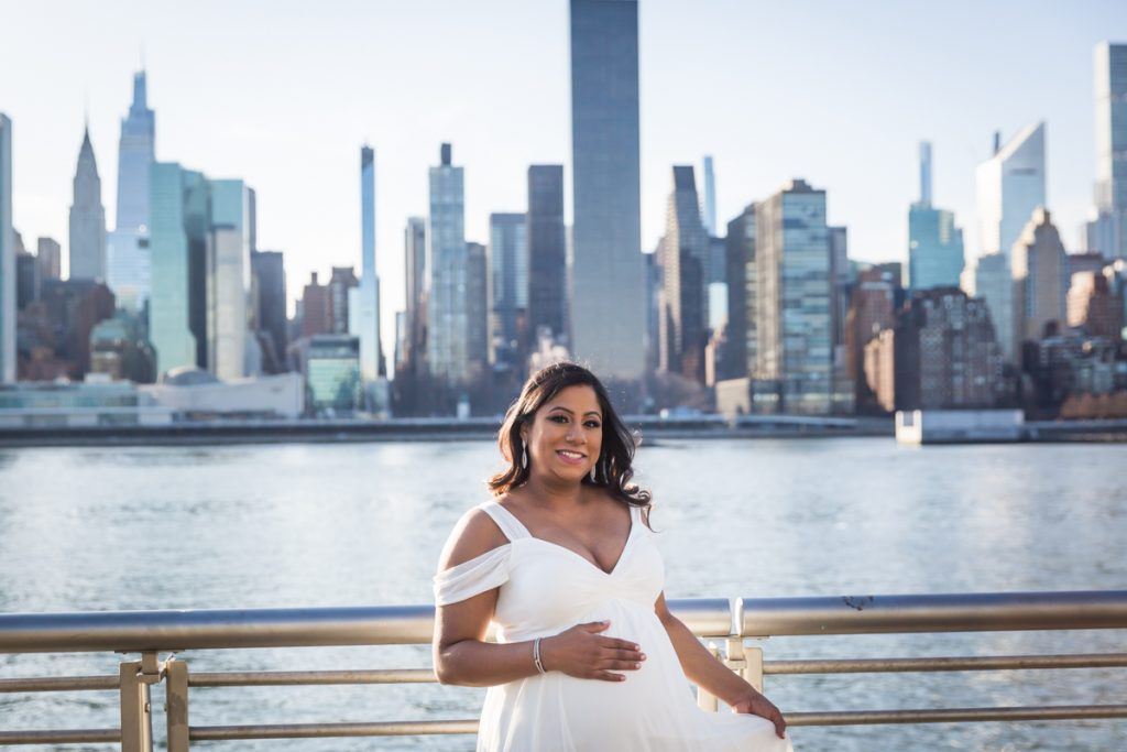 Mother to be wearing white, flowy gown in front of NYC waterfront