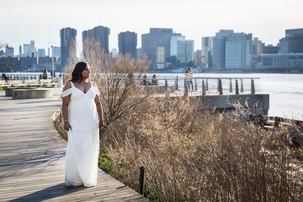 Pregnant woman in white gown walking along boardwalk during a Long Island City maternity portrait session