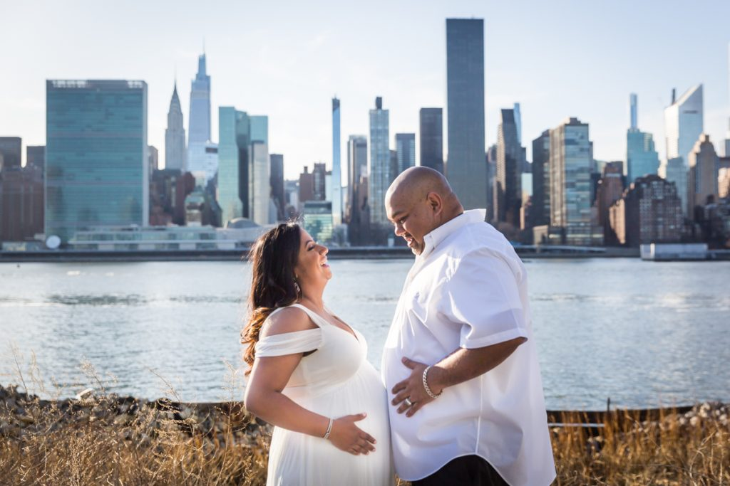 Couple comparing stomachs during a Long Island City maternity portrait session
