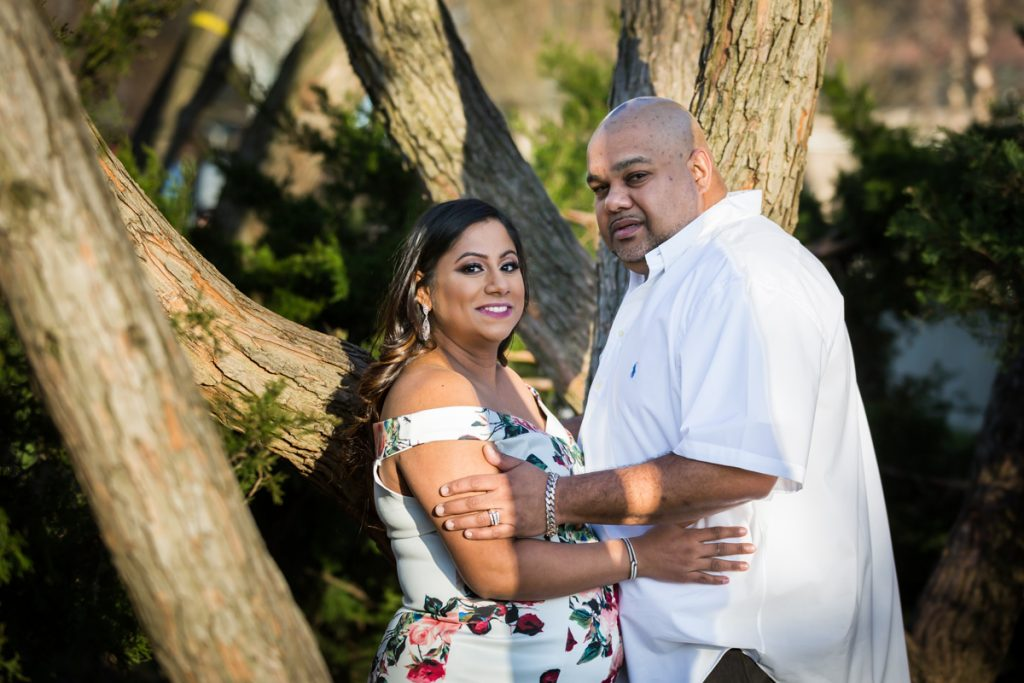 Expectant couple standing in front of trees