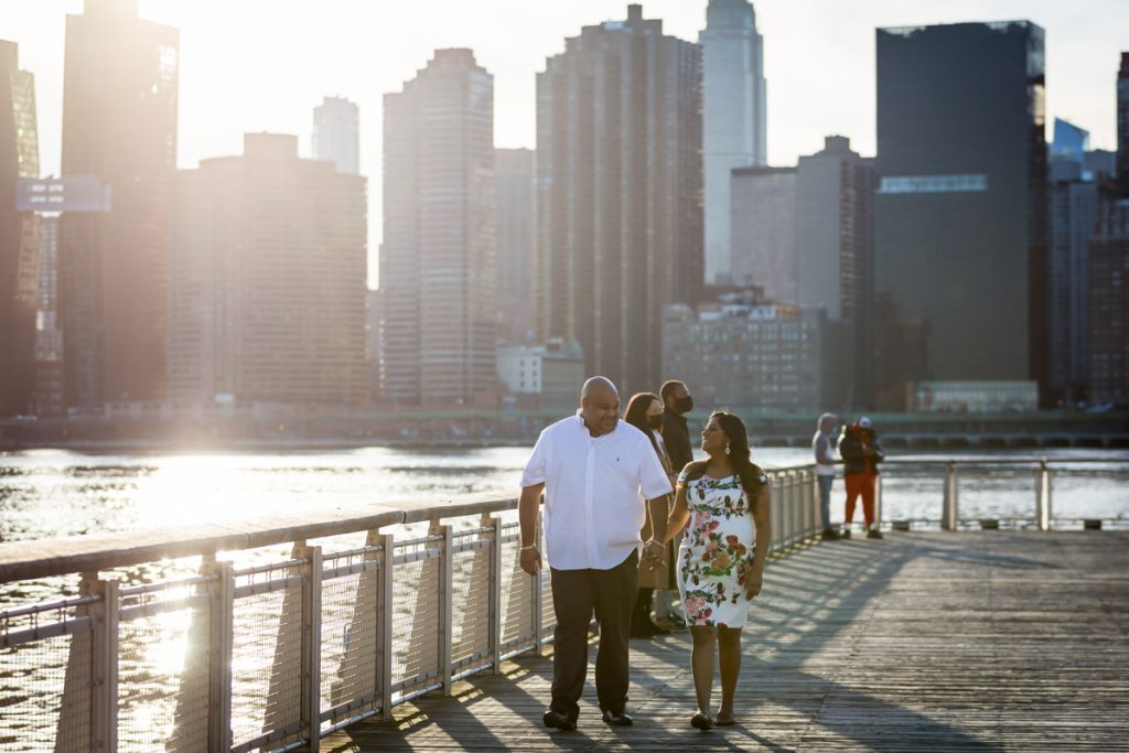 Couple walking along pier during a Long Island City maternity portrait session