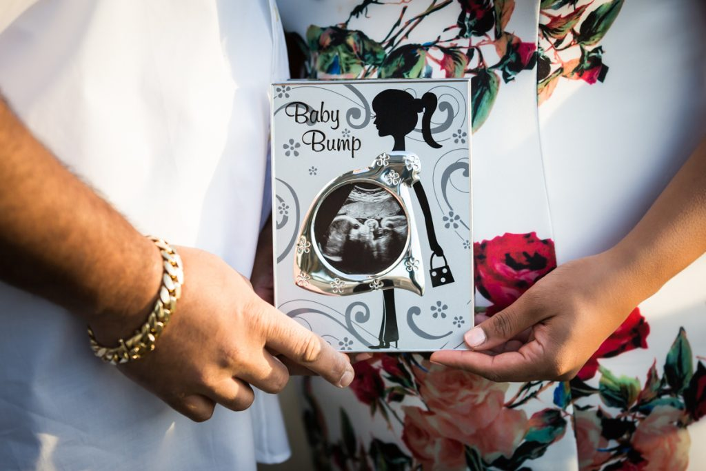 Close up of couple holding framed photo of sonogram