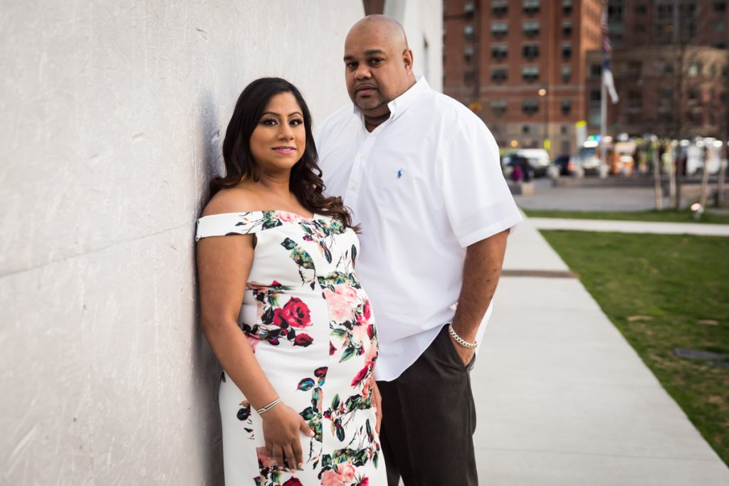 Expectant couple standing in front of white wall
