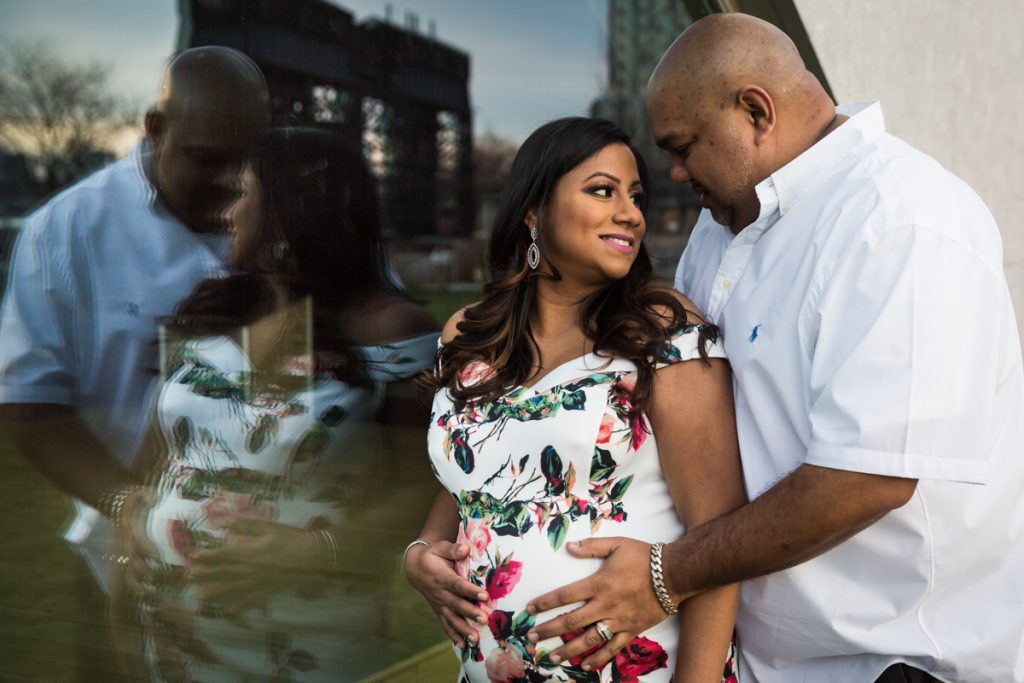 Couple reflected in window during a Long Island City maternity portrait session