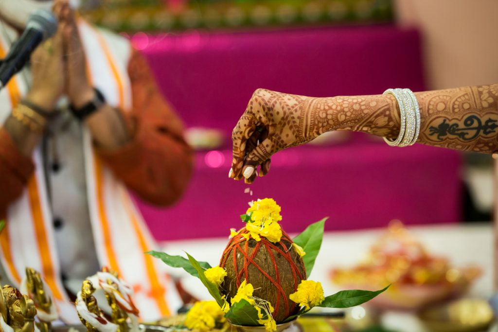 Bride's hand sprinkling flower petals on a coconut during sagai