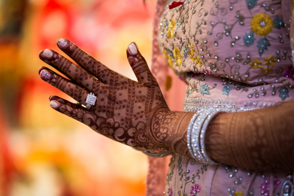 Hands of Indian bride covered in mehendi or henna