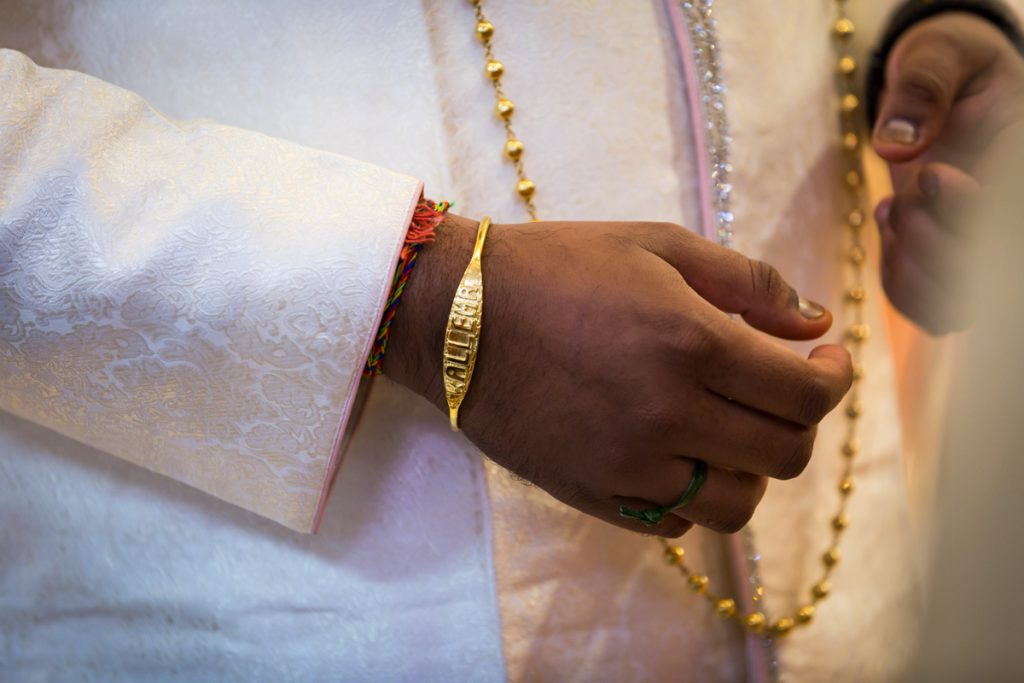 Sagai ceremony photos of groom's arm wearing gold bracelet