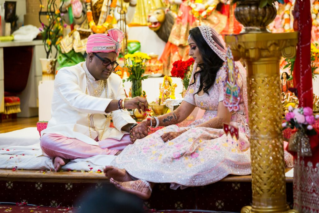 Groom sprinkling flower petals on bride during sagai ceremony