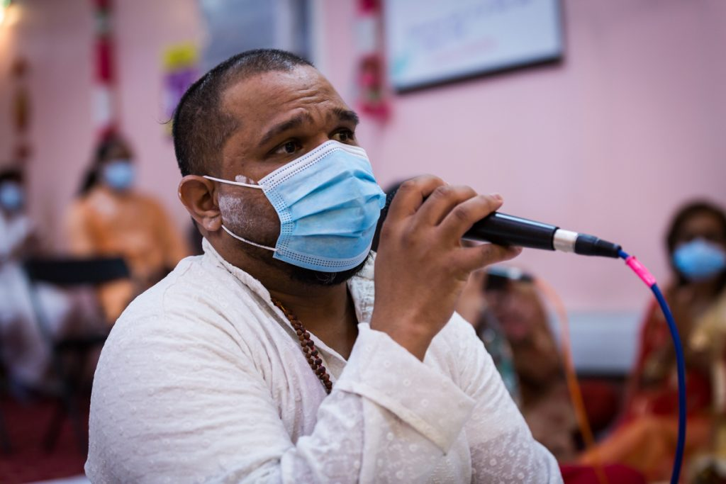 Man wearing mask singing during Hindu engagement ceremony