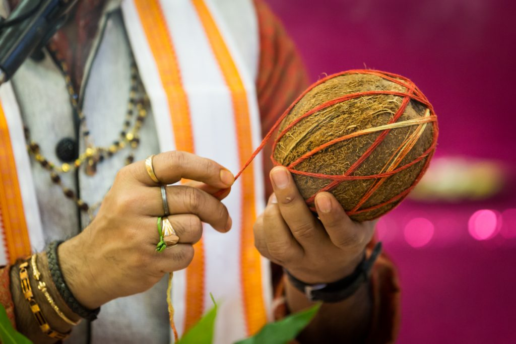 Hands of priest tying string around coconut