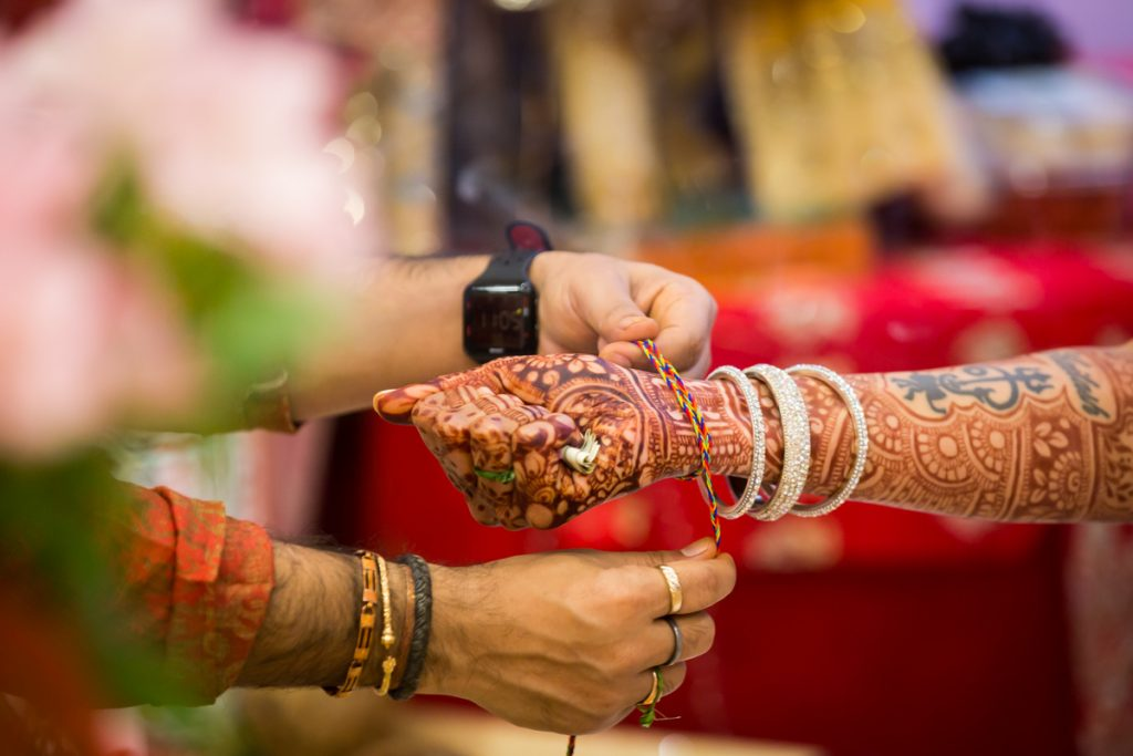Hands of priest tying string around bride's wrist during sagai
