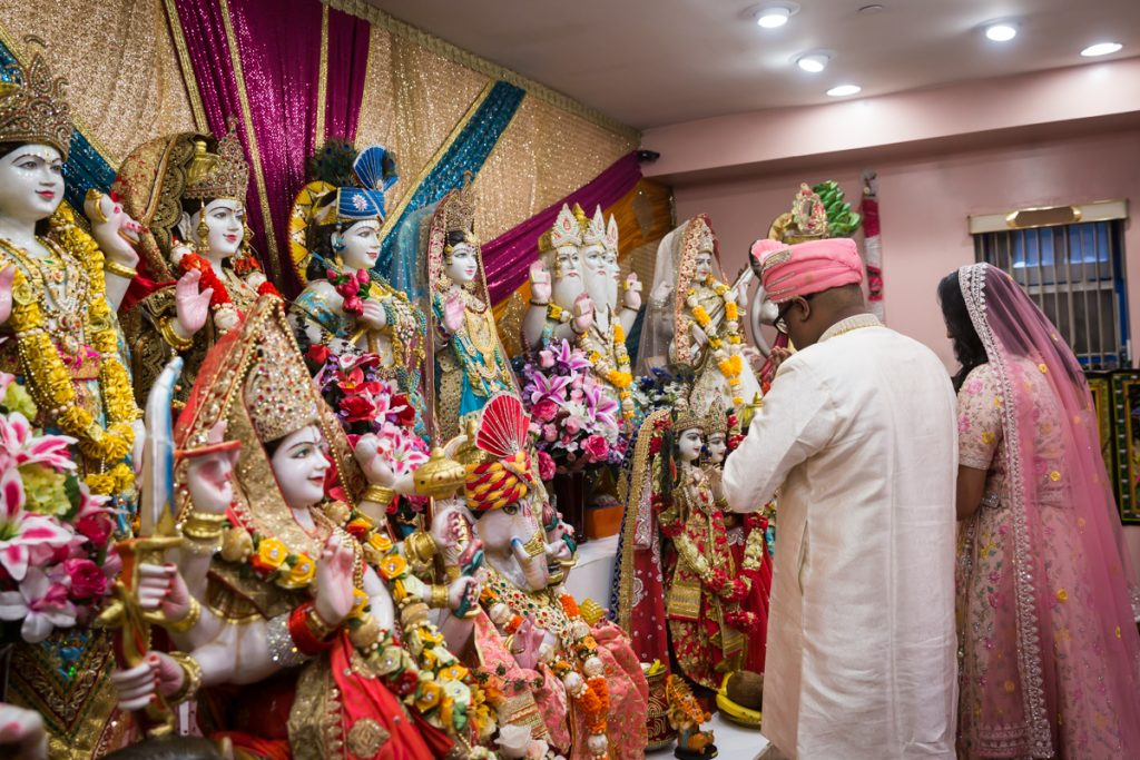 Bride and groom offering prayers to Hindu deity sculptures during sagai ceremony