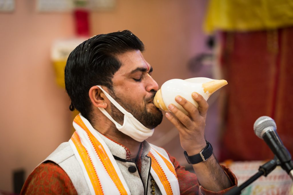 Priest blowing shell during sagai ceremony
