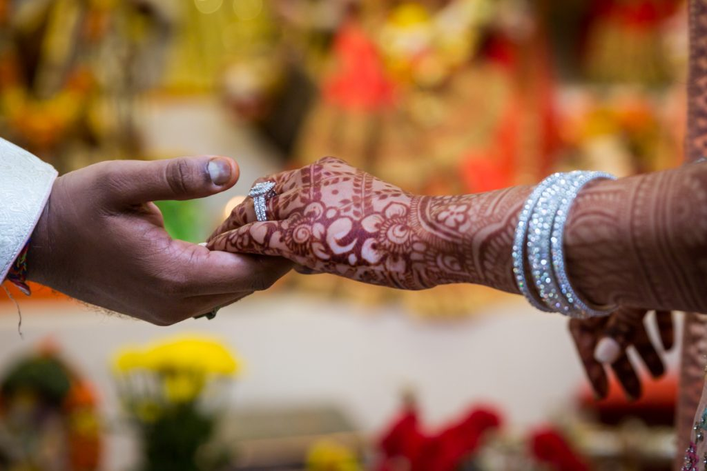 Close up of groom holding bride's hand covered in henna