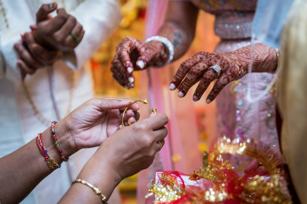 Close up of hands holding jewelry during sagai ceremony