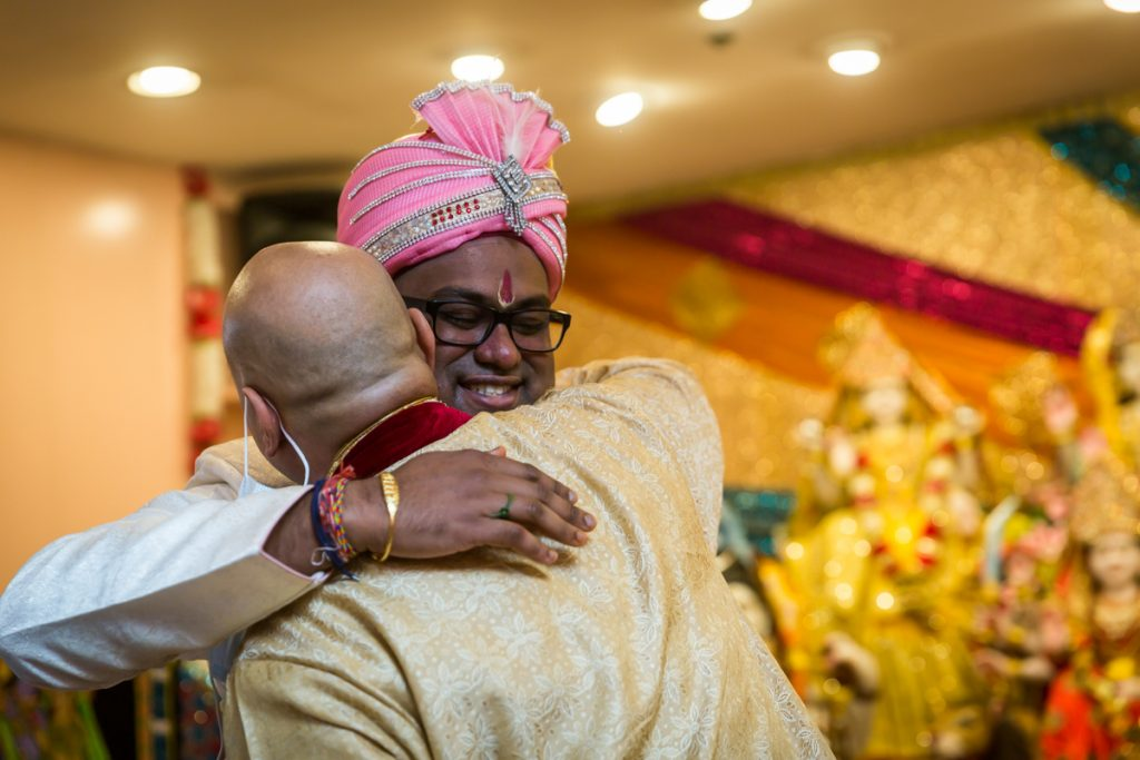 Groom hugging bride's father during Hindu engagement ceremony