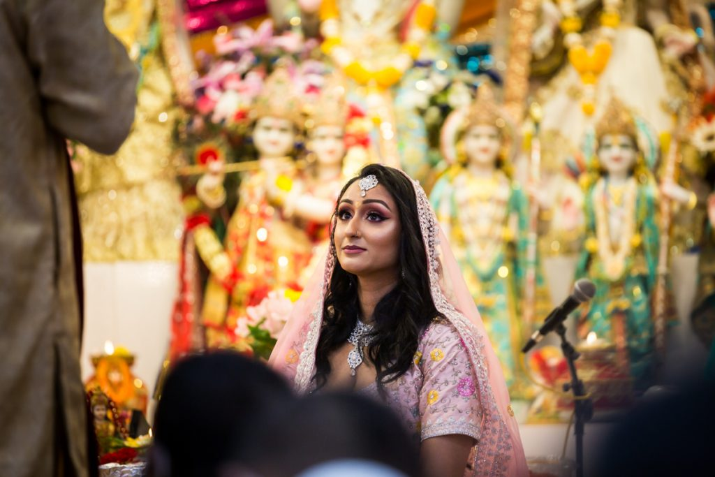 Bride listening to speeches during Hindu engagement ceremony