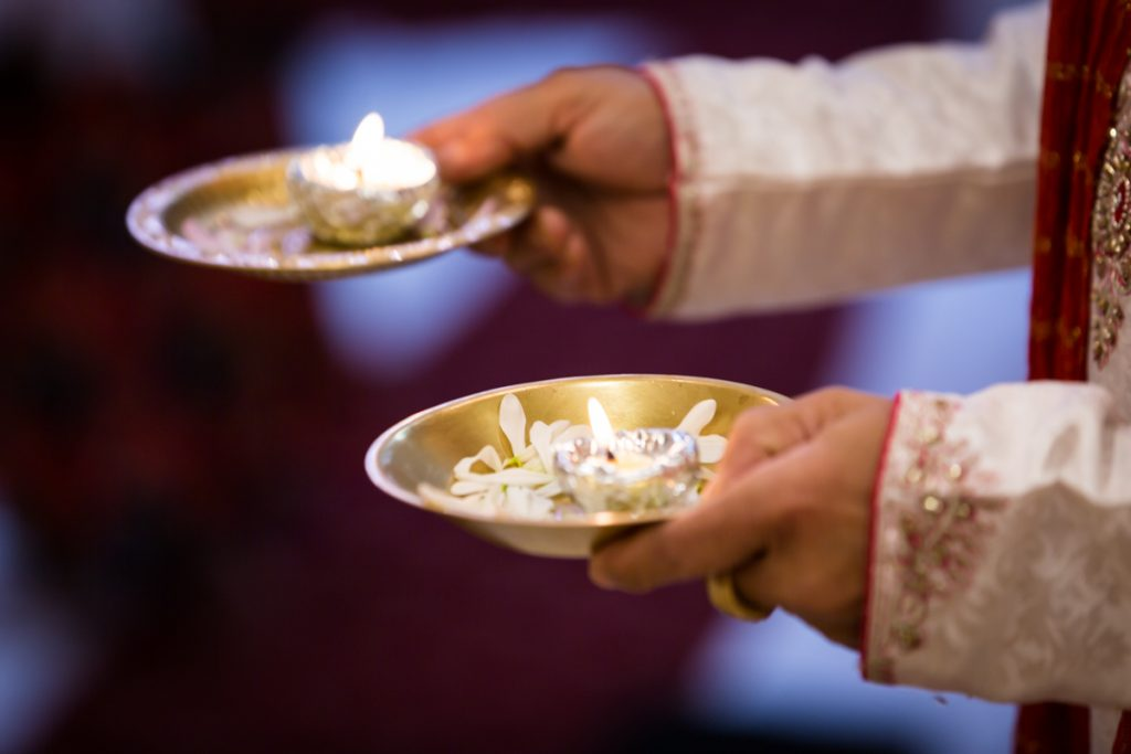 Close up of hands holding gold plates with candles