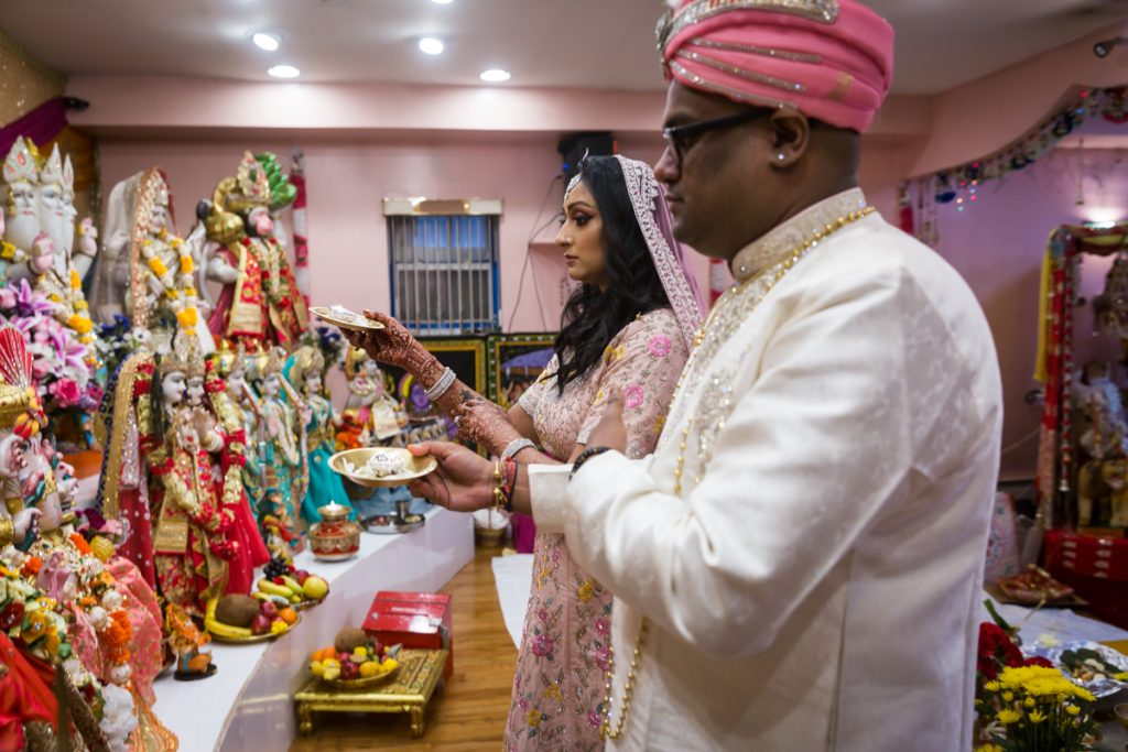 Couple holding candles in front of Hindu deity sculptures during sagai ceremony