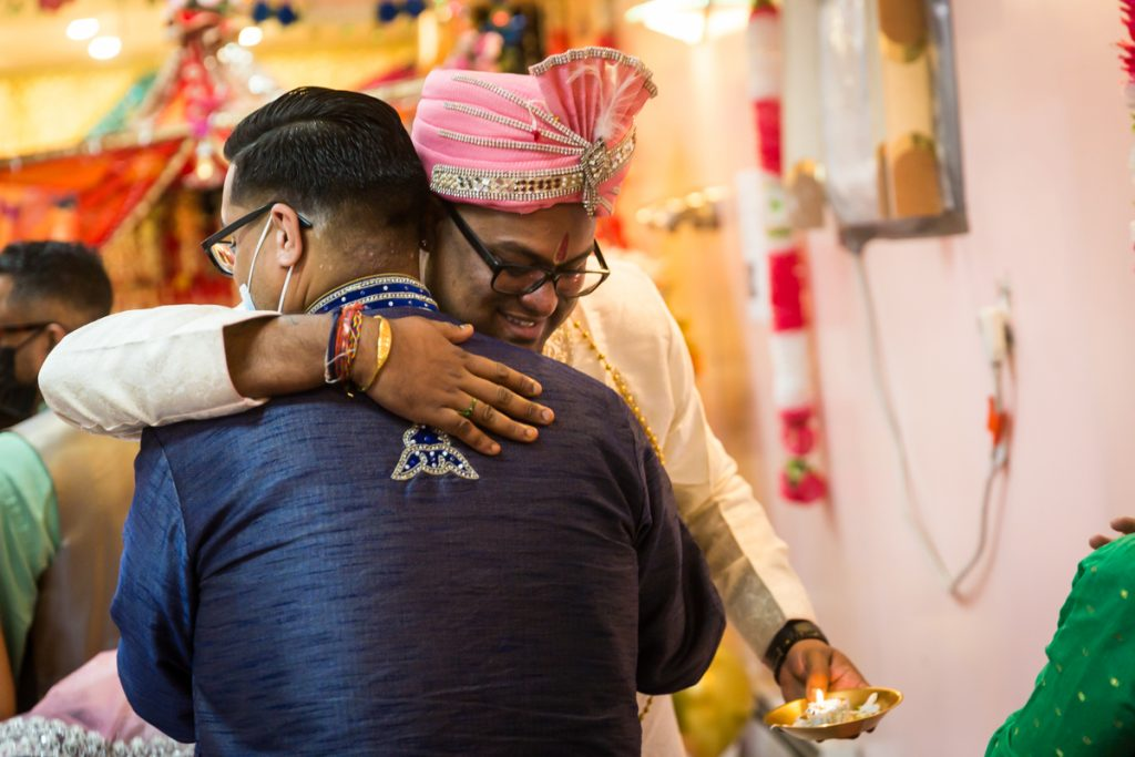 Groom hugging male guest after Hindu engagement ceremony