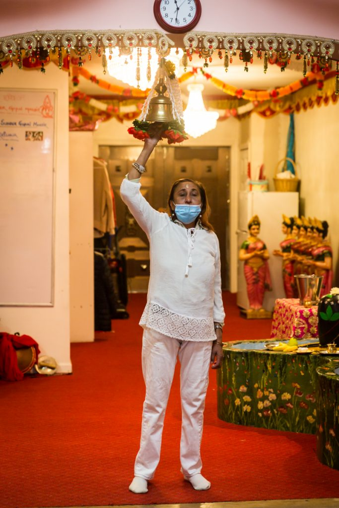 Woman in white suit ringing bell during sagai ceremony