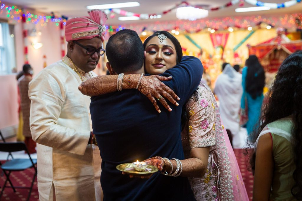 Bride hugging male guest after Hindu engagement ceremony