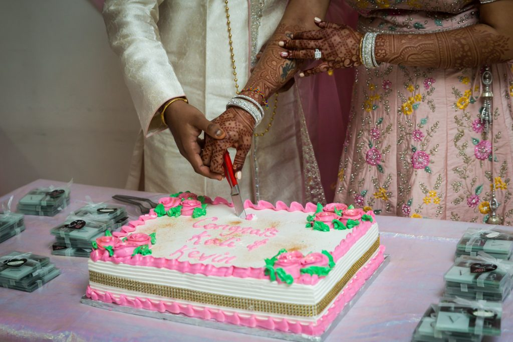 Close up of bride and groom cutting cake