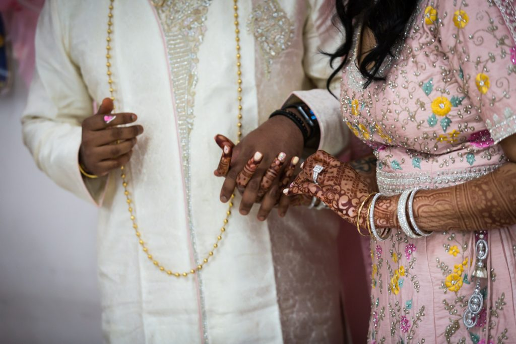 Close up of bride and groom holding hands during engagement reception
