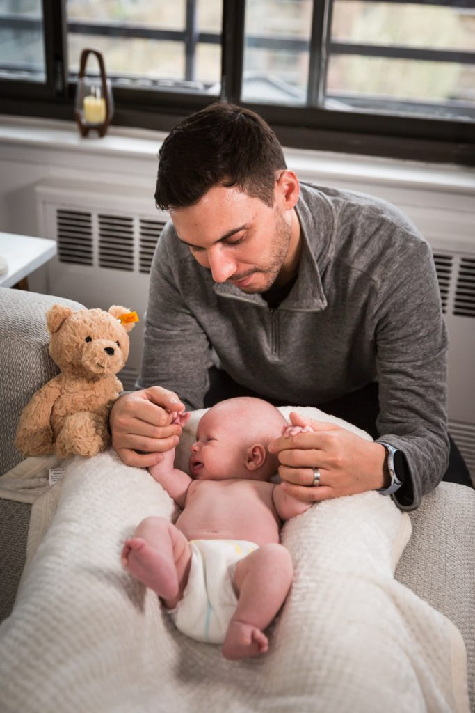 Father holding newborn baby's hands