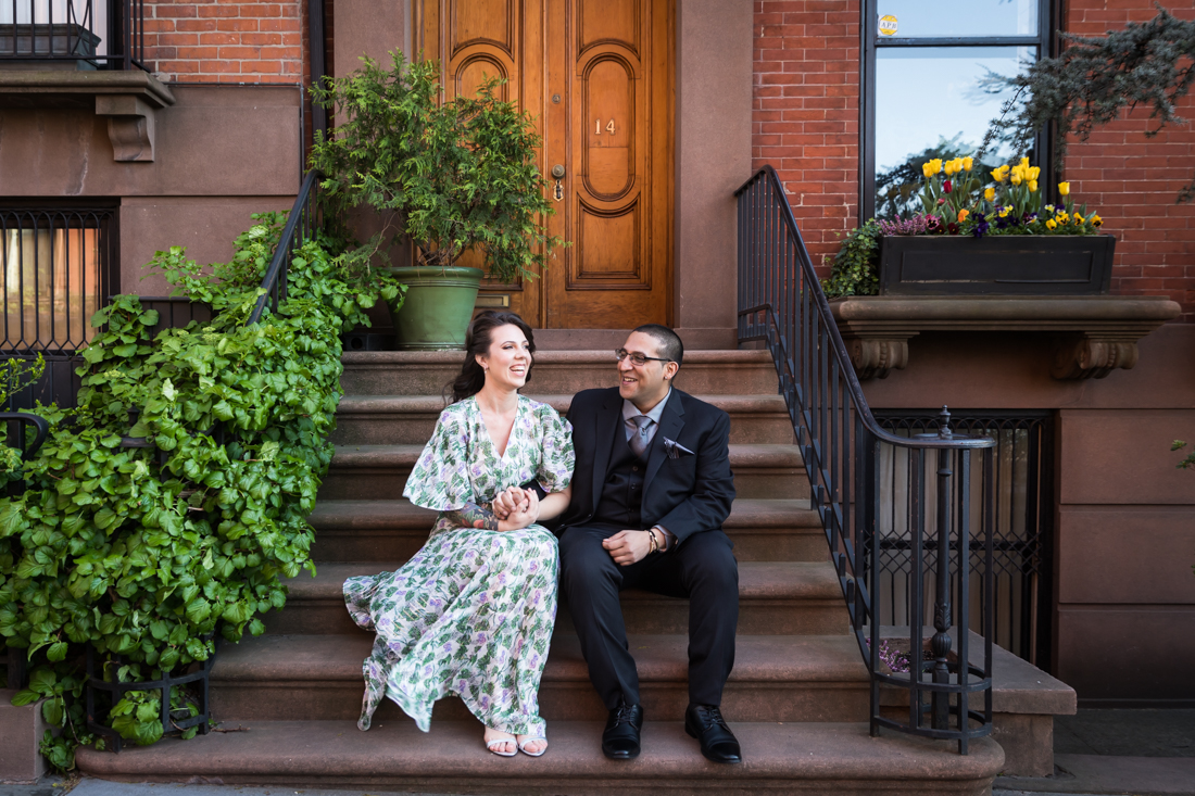 Couple sitting on brownstone steps during a Brooklyn Heights Promenade engagement photo shoot
