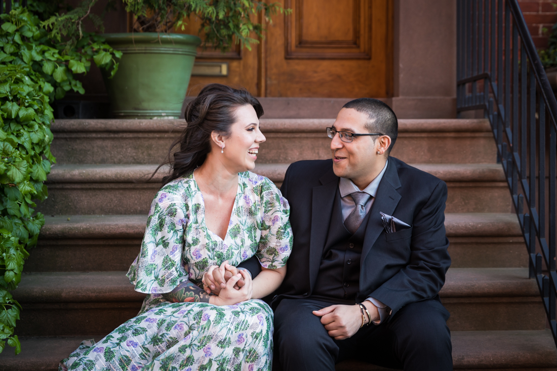 Couple laughing on brownstone steps during a Brooklyn Heights Promenade engagement photo shoot