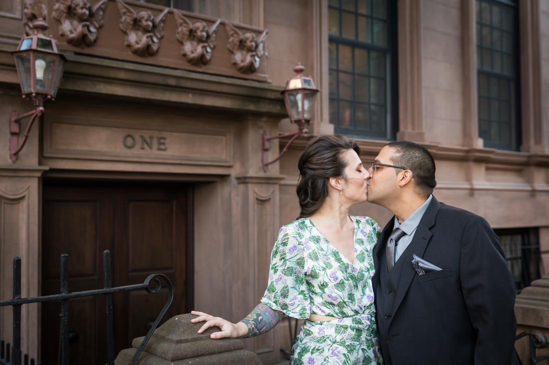 Couple kissing in front of brownstone during a Brooklyn Heights Promenade engagement photo shoot